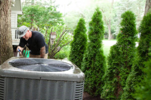 HVAC service professional cleaning an outdoor HVAC unit