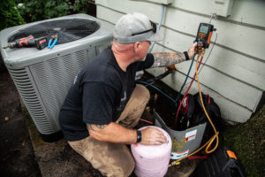 HVAC technician servicing an air conditioner