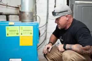 HVAC technician diagnosing a furnace issue